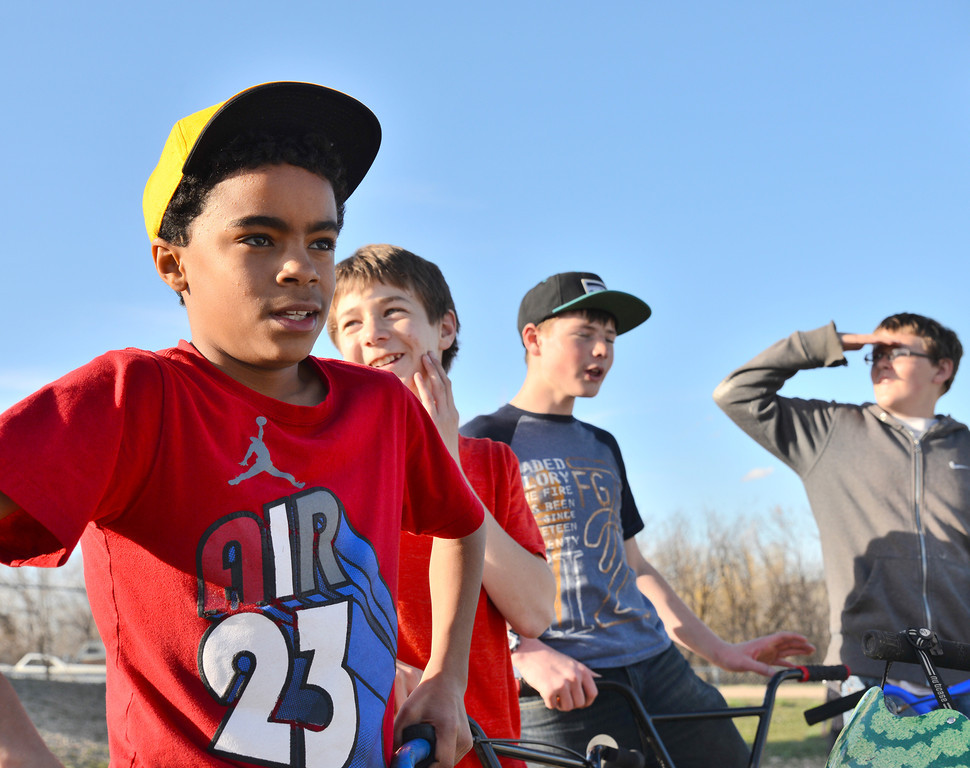 Sheridan seventh grader Matthew Cleavland, left, stands over his bike as the other youth talk about BMX jumps Thursday evening at Sheridan Skate Park. The youth have been using the Skate Park over the past month, sometimes shoveling snow and sweeping away gravel to make it safe for skateboards.