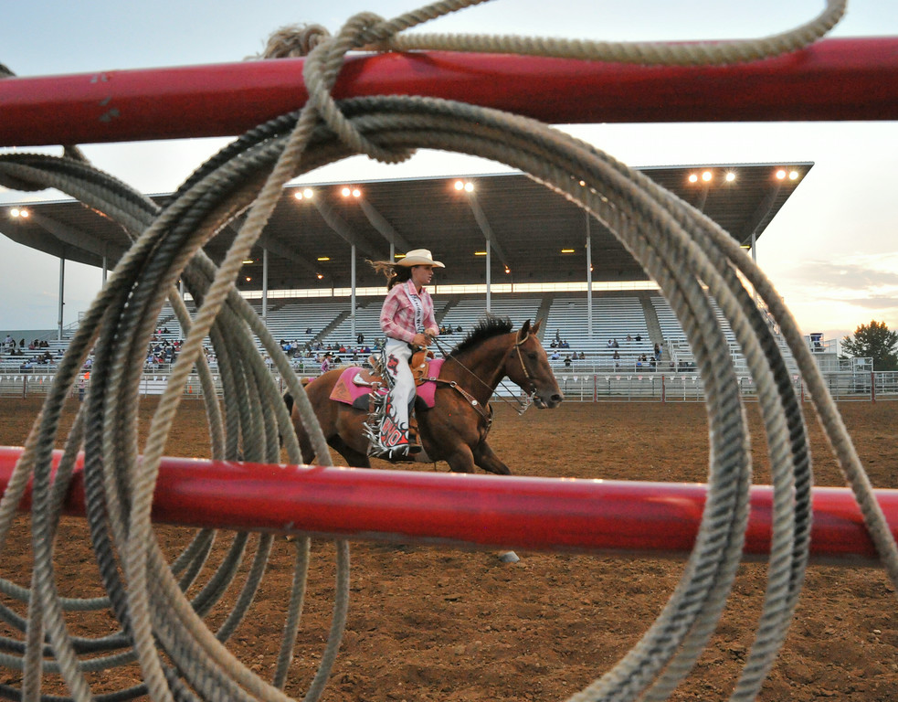 A Sheridan WYO Rodeo Royalty member directs a calf to the bottom of the arena in the breakaway roping event during the Sheridan County Rodeo Friday night at the Sheridan County Fairgrounds. The Sheridan Press|Justin Sheely.