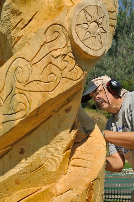 David Peterson works on his latest wood carving from a tree Tuesday morning at Kendrick Park. Peterson describes the piece as a compass made into a helix with representations of the four winds, North, South, East, and West. Each direction also indicates one of the four seasons. Peterson hopes to finish the carving soon, as this the last out of seven woodcarvings in Kendrick Park. The carvings were made from tree stumps after the city cut down a number of damaged trees during the winter of 2013. Peterson began the art project in the summer of 2013. His woodcarvings can be viewed throughout Kendrick Park. The Sheridan Press|Justin Sheely.