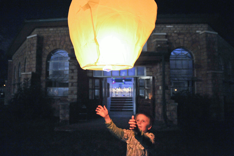 Brodie Jurgens releases a sky lantern during a private wedding party Saturday night at the Sheridan County Fairgrounds. The lanterns work like a hot air balloon. The fuel cell burns to fill the tissue balloon with hot air until the lantern is able to rise into the sky. The Sheridan Press|Justin Sheely.
