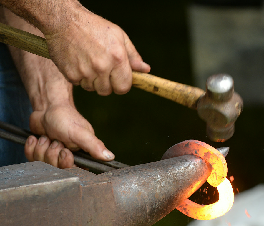 A competitor hammers away at a hot horseshoe for the the World Championship Blacksmiths competition during Don King Days at the Big Horn Equestrian Center. 70 competitors came from several countries across the globe to compete at the horse show competition. This is the third stop on a five-stop championship tour which ends at the world championships in Orlando, Florida, this December. The Sheridan Press|Justin Sheely.