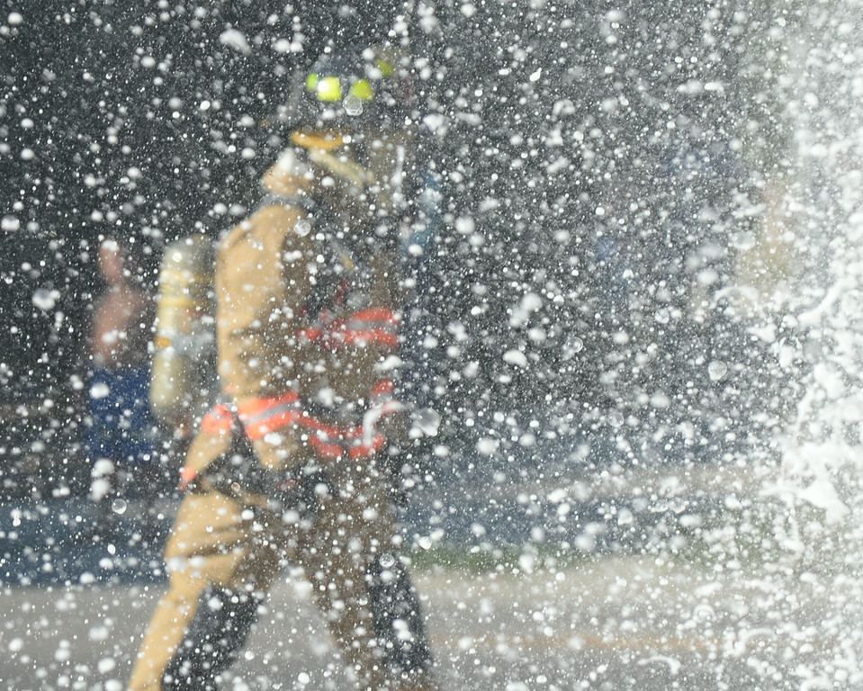 A Sheridan Fire-Rescue firefighter walks past falling foam back spray from the Ace Radiator Building in response to a structure fire Thursday evening on the corner of E. Fifth Street and Custer Street. Sheridan Fire-Rescue and Goose Valley Fire Department responded to the call with Rocky Mountain Ambulance supporting. No injuries were reported after the incident. The Sheridan Press|Justin Sheely.
