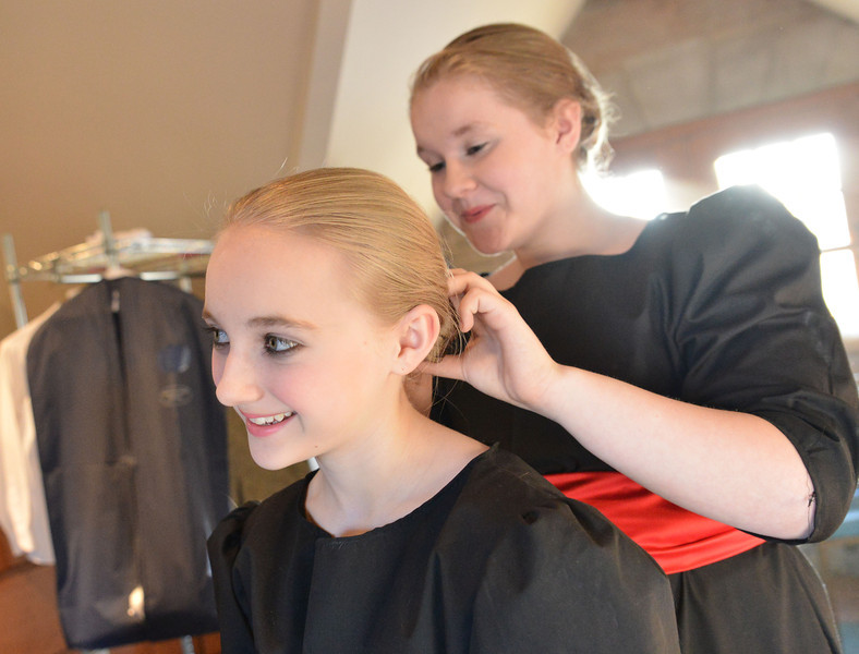 Dayla Broyles, left, holds still as Cheyenne Feley pulls back her hair in the dressing room before the Fort Mackenzie High School students' performance of 'Murder Twice Baked' Thursday evening at the Carriage House Theater.
