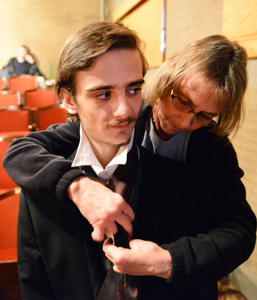 """Cindy Wiest reaches over Michael O'Kelly's shoulders to tie on a tie during a rehearsal for the Fort Mackenzie High School's """"Murder Twice Baked"""" Thursday at the Carriage House Theater."""