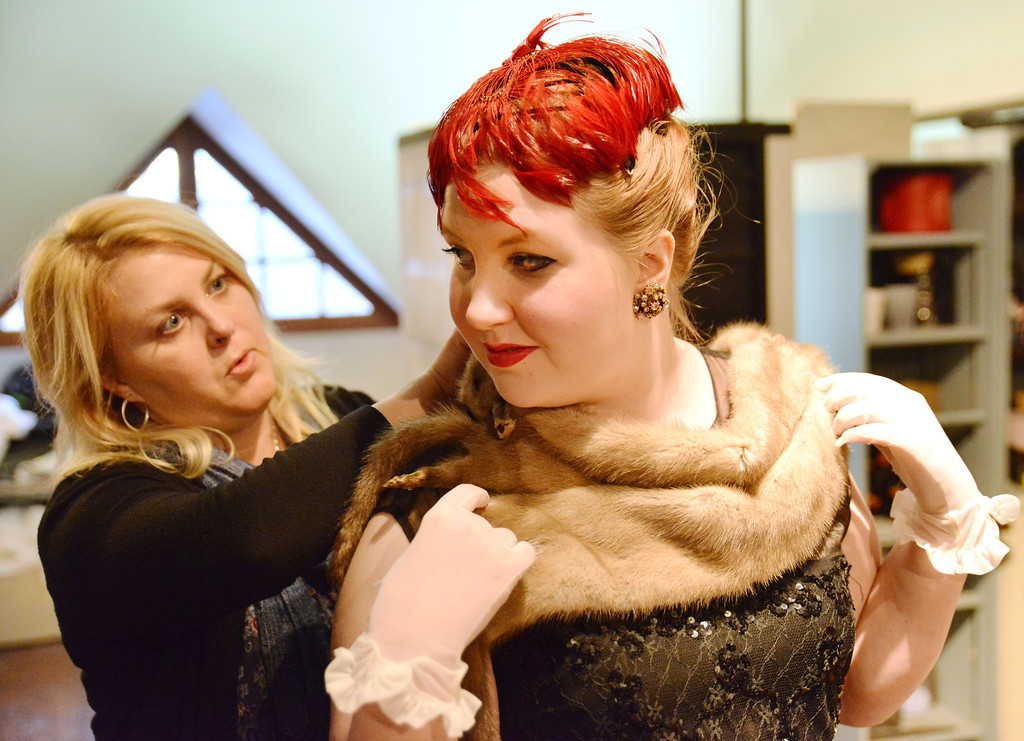 Costume designer Shelley Reinke makes an adjustment on Ashley Velos, as 'Lady Brentwood,' in the dressing room before the Fort Mackenzie High School students' performance of 'Murder Twice Baked' Thursday evening at the Carriage House Theater.