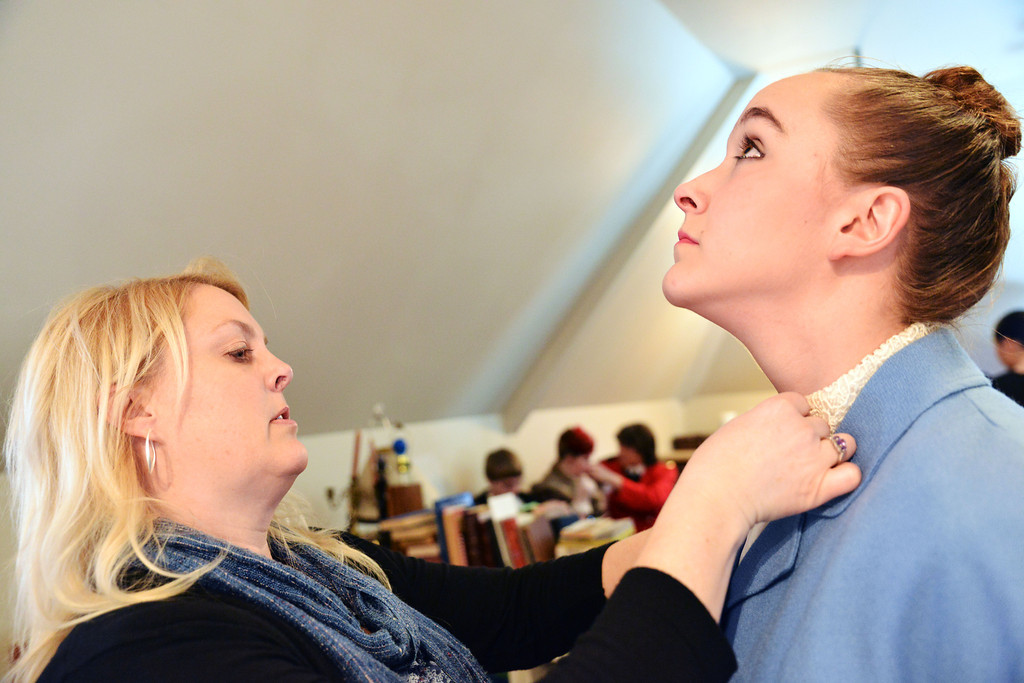 Costume designer Shelley Reinke makes adjusts a the collar on Jessica Paulson, as 'Miss Poppy,' prior to the Fort Mackenzie High School students' performance of 'Murder Twice Baked' Thursday evening on the second floor of the Carriage House Theater.