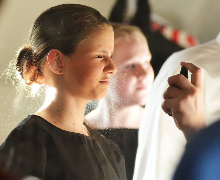 Bailey O'Leary closes her eyes as another cast member sprays her with a spray bottle in the dressing room before the Fort Mackenzie High School students' performance of 'Murder Twice Baked' Thursday evening at the Carriage House Theater.