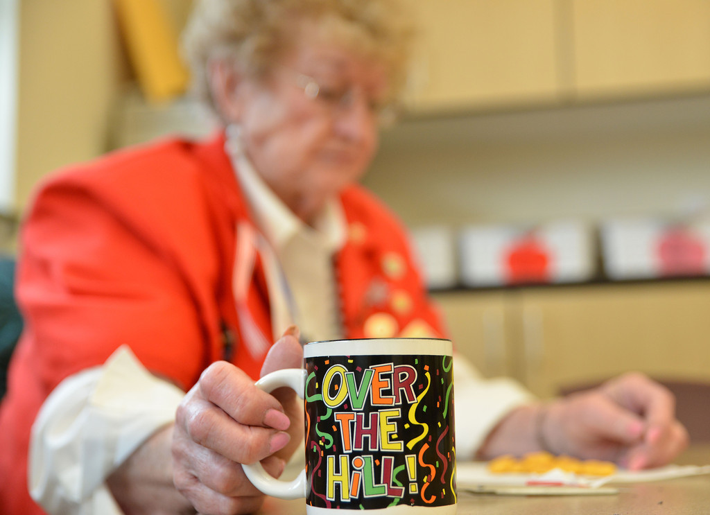 Foster Grandparent Ruth Foster drinks from her coffee mug as the students take a break during recess Wednesday at Woodland Park Elementary School.