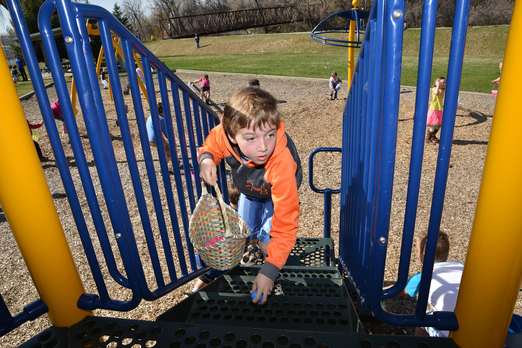 Austin McFaul, 10 hunts on the playground equipment during the Sheridan Recreation District Easter Egg Hunt Eggs-Travaganza Saturday morning at Thorne-Rider Park.