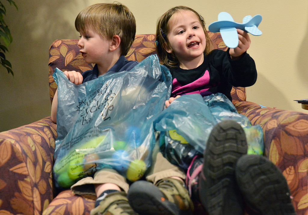 Wesson Conraads, left, sits with Mikayla Martin as she plays with a toy airplane after the Easter Egg hunt Tuesday morning at the Emeritus at Sugarland Ridge. The pre-kindergarten students from Holy Name Catholic School sang songs for the Sugarland residents before embarking on an egg hunt through out the building. Sugarland residents helped with the event by handing out candy and toys during the event.