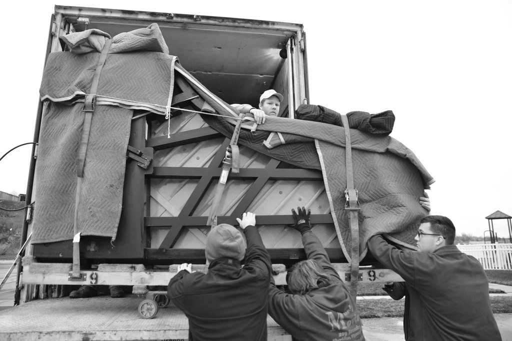 Mac's Moving employee Mike Logan, top, looks over the 9-foot long Bechstein Grand Piano as the team prepares to move it off the truck last Wednesday at First Baptist Church in Sheridan.