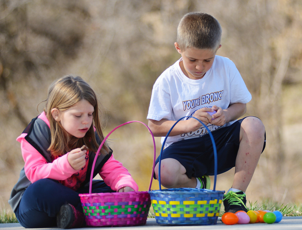 7-year-old Dannielle Gilbert, left, and her brother Mark Gilbert, 8, sort through their loot after the Sheridan Recreation District Easter Egg Hunt Eggs-Travaganza Saturday morning at Thorne-Rider Park.