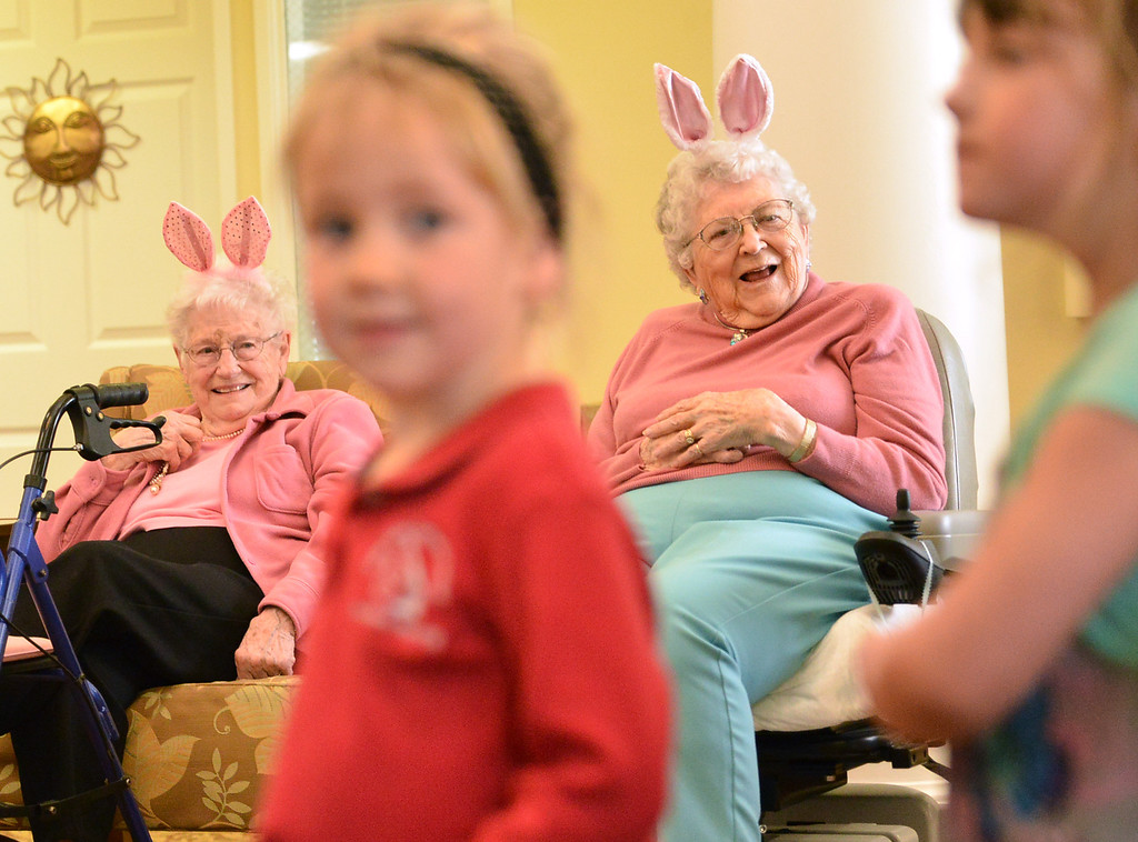 Sugarland Ridge residents Jean Thies, left, and Barbara Oedekoven watch as children from the Holy Name Catholic School pour into the lobby Tuesday morning at the Emeritus at Sugarland Ridge. The pre-kindergarten students from Holy Name Catholic School sang songs for the Sugarland residents before embarking on an egg hunt through out the building. Sugarland residents helped with the event by handing out candy and toys during the event.