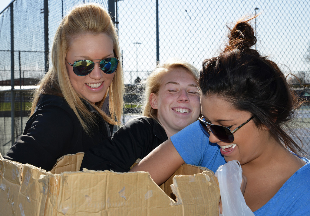 Madison Farr, left, Drew Dafoe, and Becky Bridger reach into a box of filled plastic eggs to scatter around the area for the Sheridan Recreation District Easter Egg Hunt Eggs-Travaganza Saturday morning at Thorne-Rider Park.