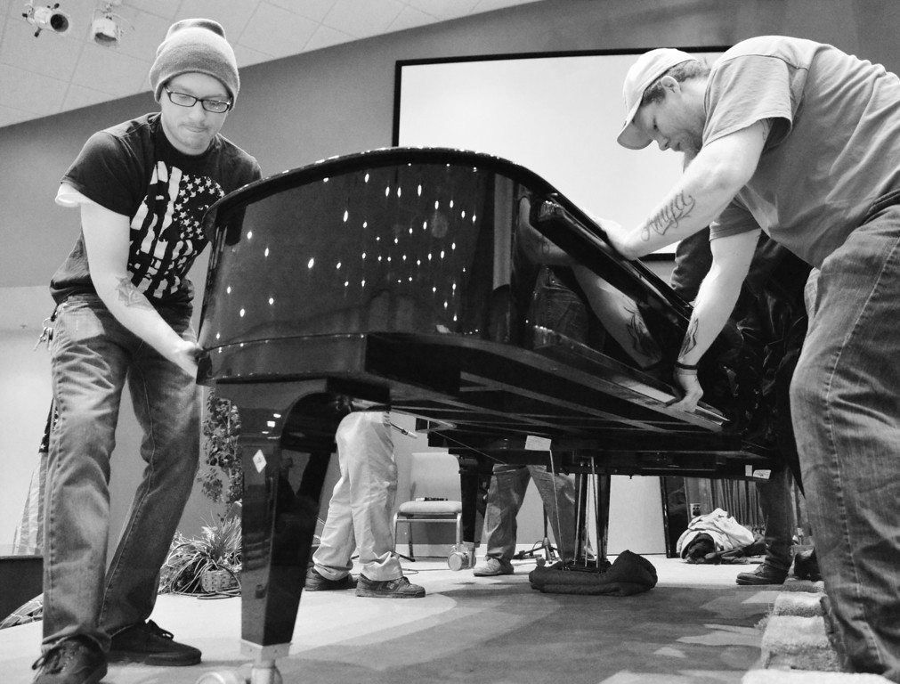 """Mac's Moving employees Tyler McKenzie, left, and Mike Logan set down the 1400-pound Bechstein Grand Piano on the stage last Wednesday at First Baptist Church in Sheridan. The 9-foot long piano was purchased for use by the congregation's regular worship services and to attract community classical music events in collaboration with the Sheridan Arts Council. """"We want to fill a hole in the artistic calendar in Sheridan."""" Pastor John Craft said. The primary reason for the purchase was to open up the building to classical music presentations. The first classical music event is presented by the Piatigorsky Foundation, which is set for this May 8, at 7 p.m. and is free to the public. The Classical Music Concert will feature Katie Calcamuggio, a mezzo-soprano, and John Elam on piano."""