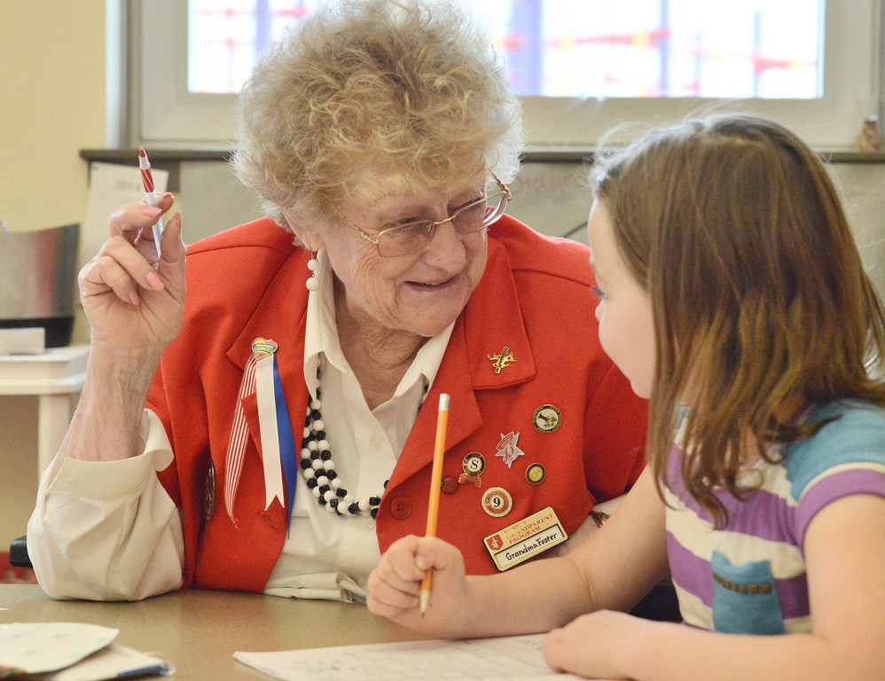 """Foster Grandparent Ruth Foster smiles at Erin Hoffman as she volunteers in Annie Wollenzien's first grade classroom Wednesday at Woodland Park Elementary School. The 76-year-old """"Grandma Foster"""" has been volunteering with the Foster Grandparent Program for 12 year, six of which has been in Wollenzien's classroom. The Foster Grandparent Program is a national program that encourages people 55 years or older to stay active with youth as mentors and positive role models. There are currently 15 active Foster Grandparents in the Sheridan-Johnson and Campbell County region. The qualifying volunteers work for a small stipend and some benefits such as earned vacation, paid holiday, and travel expenses. Wollenzien said that her students love having Grandma Foster in the classroom. Foster helps the first grade students with reading, writing, and math. Wollenzien recalls that Foster used to keep a schedule book for the children who wanted to sit with her in the cafeteria during lunchtime, so all of the students could take turns. """"I'll never give her up."""" Wollenzien said."""