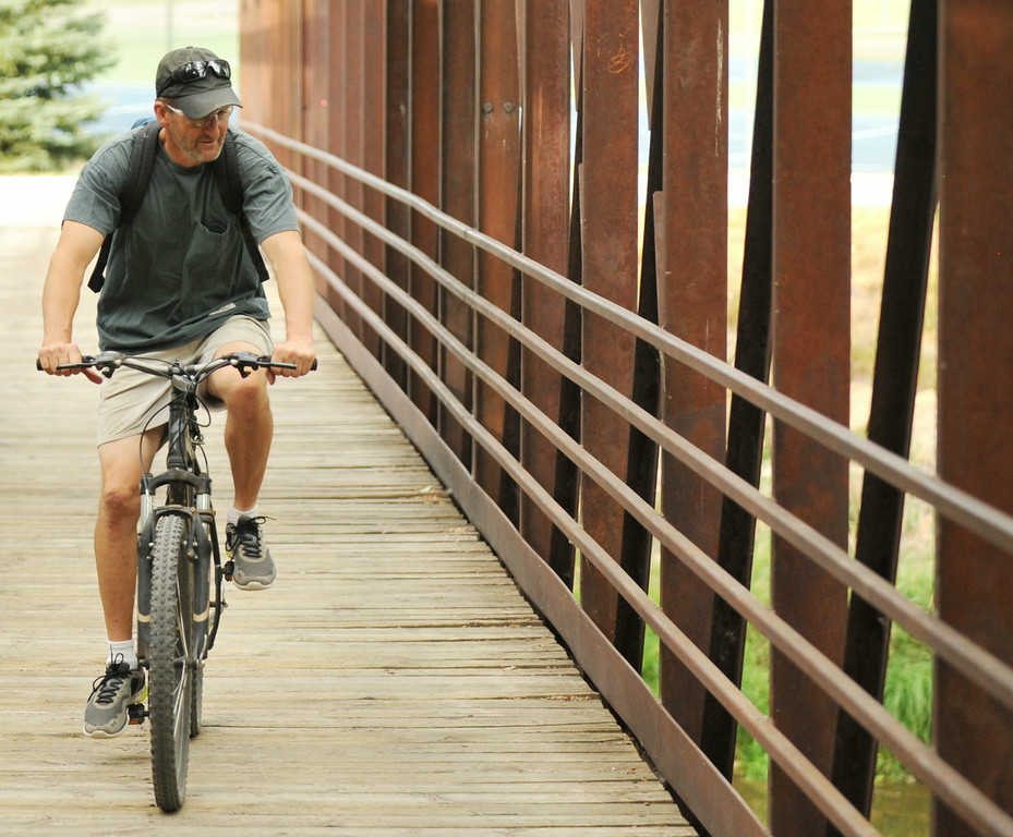 Bud Lee peddles his bike up the bridge over the Goose Creek near Thorne-Rider Park Wednesday evening.  The Sheridan Press|Justin Sheely.
