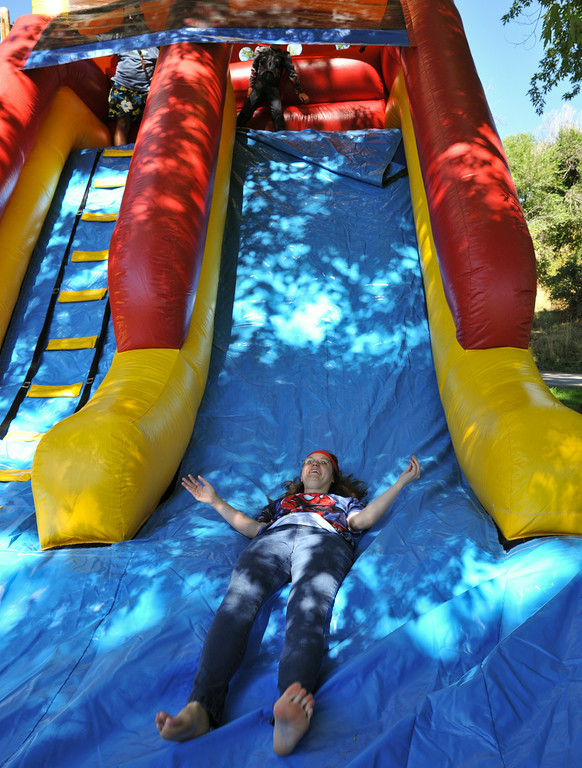 Marsha Turner laughs after sliding down the inflatable ride during the  'Superheroes in the Park' event Friday morning at Kendrick Park. The event featured fun and games for individuals with developmental disabilities or acquired brain injuries. The Sheridan Press|Justin Sheely.