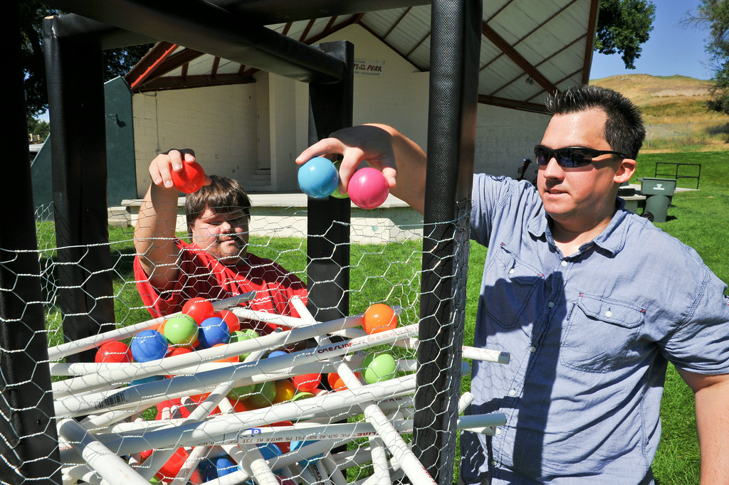 Allen Mayzsak, left, and AJ Steven set up a game for the attendees during the  'Superheroes in the Park' event Friday morning at Kendrick Park. The event featured fun and games for individuals with developmental disabilities or acquired brain injuries. The Sheridan Press|Justin Sheely.