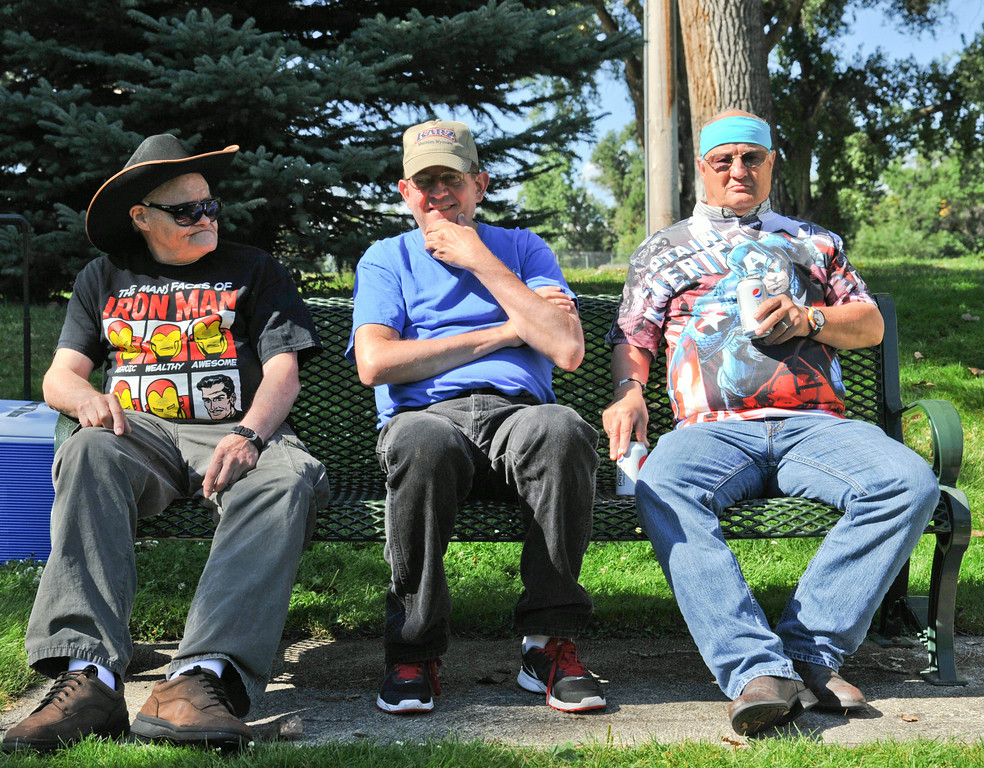 From left, Charels Parker, 76, Willie Barbula, 57, and David Shanahan, 62, sit on a bench as other attendees arrive for the 'Superheroes in the Park' event Friday morning at Kendrick Park. The event featured fun and games for individuals with developmental disabilities or acquired brain injuries. The Sheridan Press|Justin Sheely.