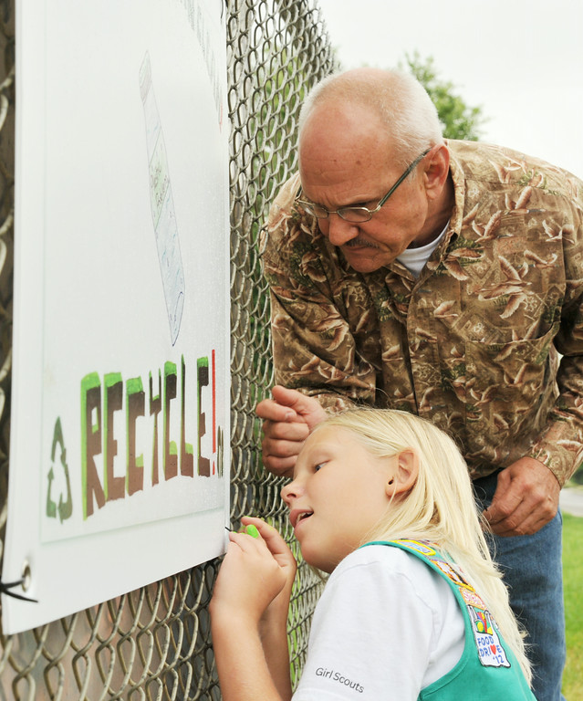 "Sheridan Mayor John Heath helps Junior Level Girl Scout Mackenzie Martini, 10, from troop 1175 tie a recycling sign on a fence by the recycling site on Bighorn Avenue Thursday afternoon. Heath was present to recognize the scouts' project. Scouts Kassidy Fisk and Mackenzie Martini had designed the sign as a ""take action"" segment of their Journeys Project this summer. The troop didn't have enough money to create the weater-proof signs that they needed for their project, so they approached the City Planning Committee this past June to pitch their idea. The City of Sheridan paid for three copies of the scout's sign to be hung at various recycling sites in Sheridan. The girls felt a need to promote recycling in the community for what Martini describes as a ""plastic problem"" littering the streets in her community. The signs can be seen around the city at near the recycling sites. The Sheridan Press
