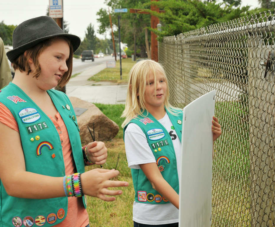 "Junior Level Girl Scouts from troop 1175 Kassidy Fisk, left, and Mackenzie Martini, both 11, hang up a printed copy of a recycling sign on a fence by the recycling site on Bighorn Avenue Thursday afternoon. The two scouts had designed the sign as a ""take action"" segment of their Journeys Project this summer. The troop didn't have enough money to create the weater-proof signs that they needed for their project, so they approached the City Planning Committee this past June to pitch their idea. The City of Sheridan paid for three copies of the scout's sign to be hung at various recycling sites in Sheridan. The girls felt a need to promote recycling in the community for what Martini describes as a ""plastic problem"" littering the streets in her community. The signs can be seen around the city at near the recycling sites. The Sheridan Press