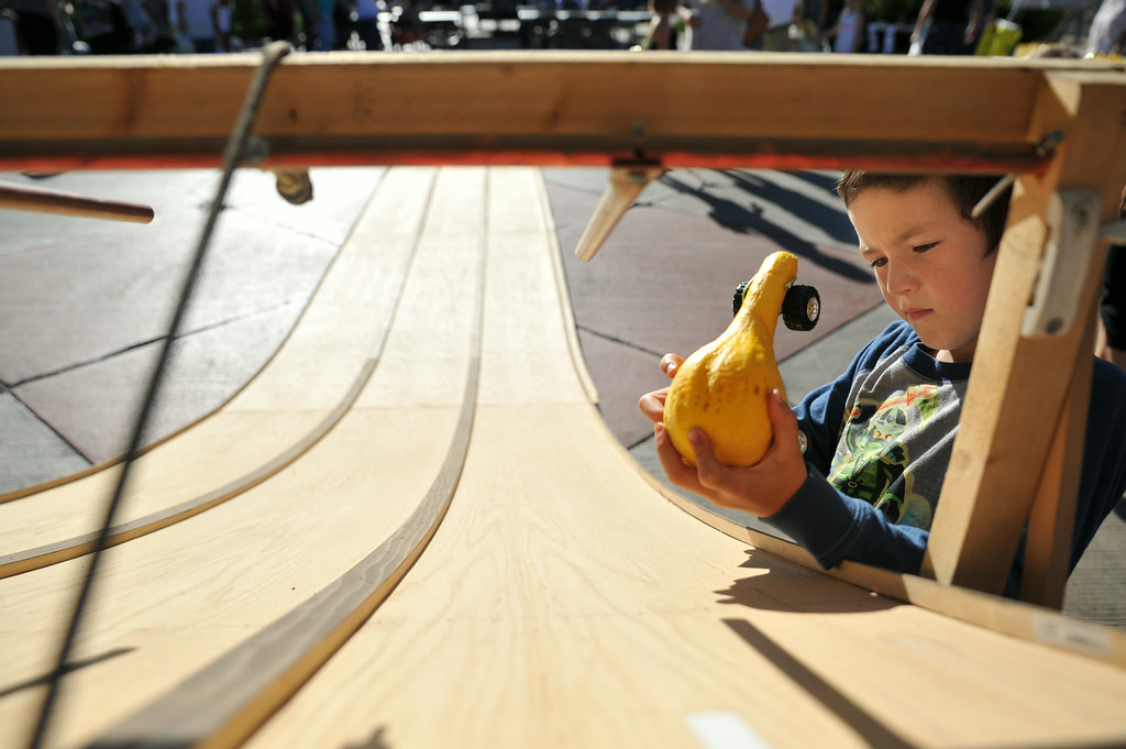 Seven-year-old Logan Mediate tests out his zucchini derby on the track for the zucchini races during the Farmer's Market Thursday evening on Grinnell Street. A spin on the traditional pinewood derby, children were invited to decorate zucchinis and tie on a set of wheels for the race. The Sheridan Press|Justin Sheely.