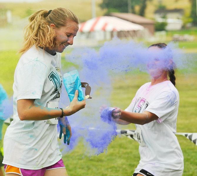 Lyndsay Grotelushen from the Sheridan community runs pass color bombers in the color run 5k during the NSI Fall Festival Saturday at NSI out on Big Goose Road. The color run was part of the fall festival in which the community was invited to participate. Normative Services currently has 73 students on campus from Montana, Wyoming, California, Nebraska, and Washington represented. The Sheridan Press Justin Sheely.
