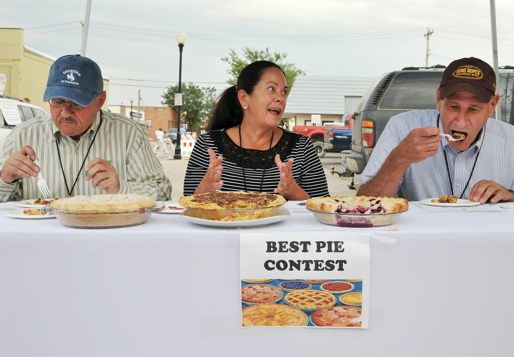 Sheridan Mayor John Heath, left, Rep. Rosie Berger, and County Commissioner Steve Maier, right, judge in the pie contest during the Farmer's Market Thursday on Grinnell Street. The pecan pie won the judges' best pie choice and the strawberry rhubarb took second. The Sheridan Press|Justin Sheely.