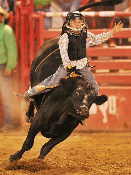 Ten-year-old Colt Welsh does an exhibition ride on a steer during the Sheridan County Rodeo Saturday night at the Sheridan County Fairgrounds arena. The Sheridan Press Justin Sheely.