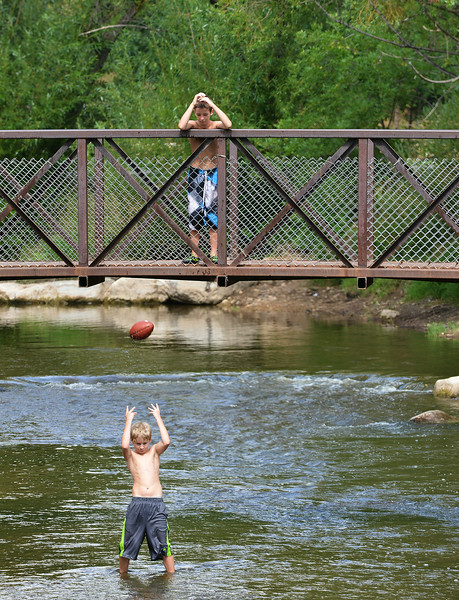 Ten-year-old Mason Sisko, below, tosses a football to Kaden Moeller, 11, on the Big Goose Creek Tuesday morning next to Kendrick Park. The youth will be starting tackle football this week via the Sheridan Recreation District. The Sheridan Press Justin Sheely.