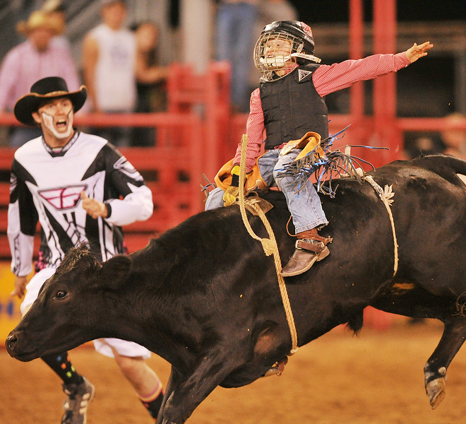 Eight-year-old Hayden Welsh does an exhibition ride on a steer during the Sheridan County Rodeo Saturday night at the Sheridan County Fairgrounds arena. The Sheridan Press Justin Sheely.
