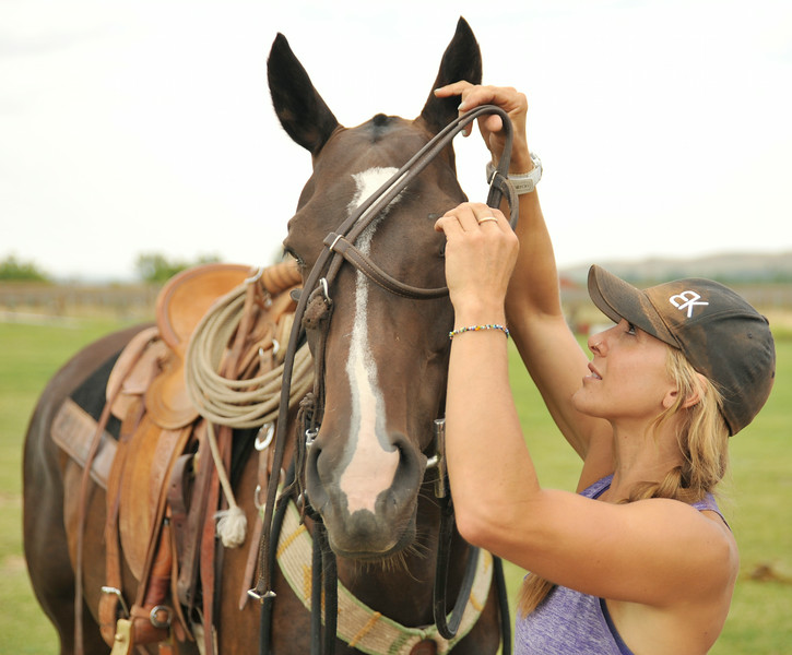 Catlin Dix of Spokane, Washington, bridles her horse 'Good Sister' for a practice at polo Thursday at the Big Horn Equestrian Center. Dix will be playing this Sunday in the women's game. The Sheridan Press Justin Sheely.