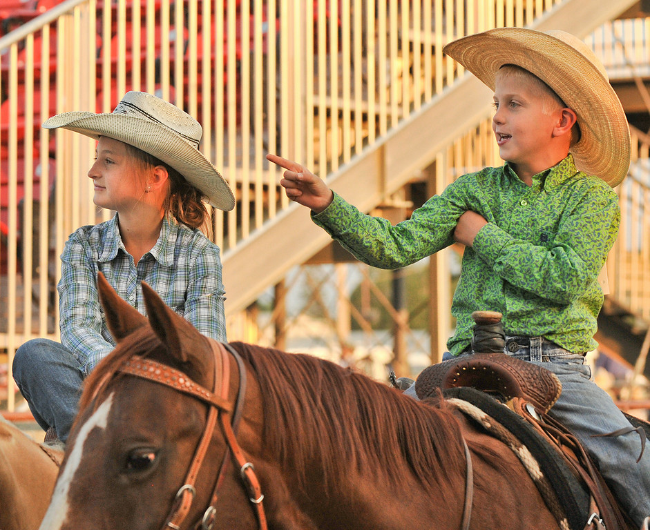 Twelve-year-old Bailey Cunningham, left, and Tuck Myers, 7, watch the saddle bronc riders compete in the arena during the Sheridan County Rodeo Friday night at the Sheridan County Fairgrounds. Cunningham and Myers were competing in barrel racing, pole bending, goat tying, and breakaway roping during the rodeo. The Sheridan Press|Justin Sheely.