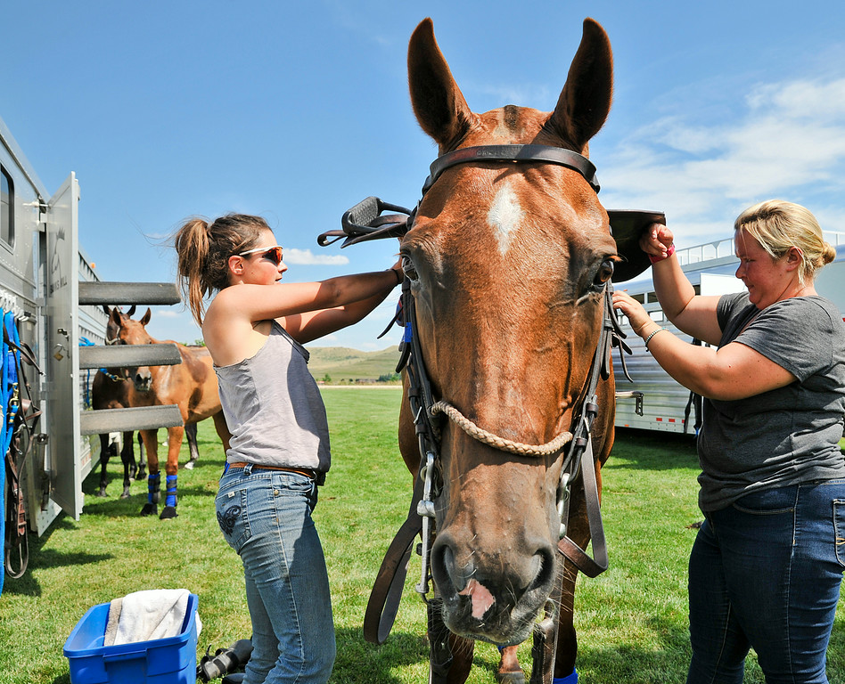 Horse groomers Faith Seville, left, and Ariel Mazur quickly prepare a horse for polo player Adam Snow during the early afternoon game Thursday at the Flying H Polo Club. The Sheridan Press|Justin Sheely.