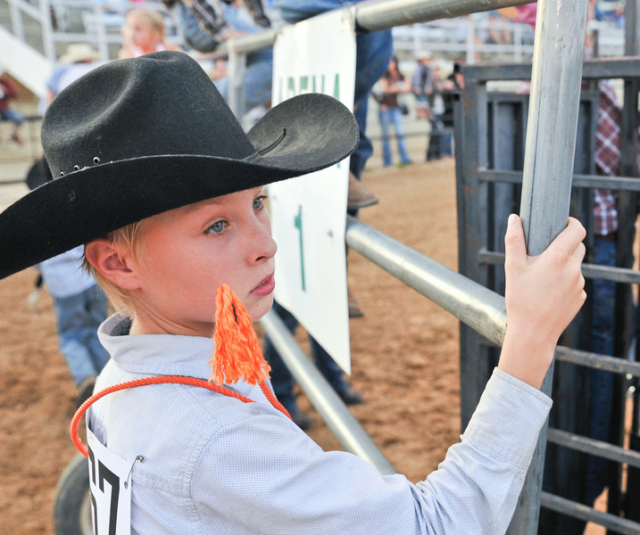 Warren Reinke opens the gate to the track for the calf riding event during the Sheridan County Rodeo Friday night at the Sheridan County Fairgrounds. The Sheridan Press Justin Sheely.