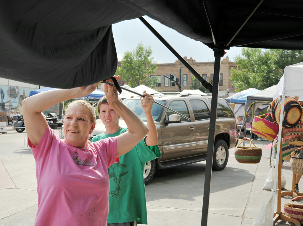Cheryl Pickering, left, and Trystan Scarpulla setup the awning over their vendor's booth table during setup for the Farmer's Market Thursday on Grinnell Street. The Sheridan Press|Justin Sheely.