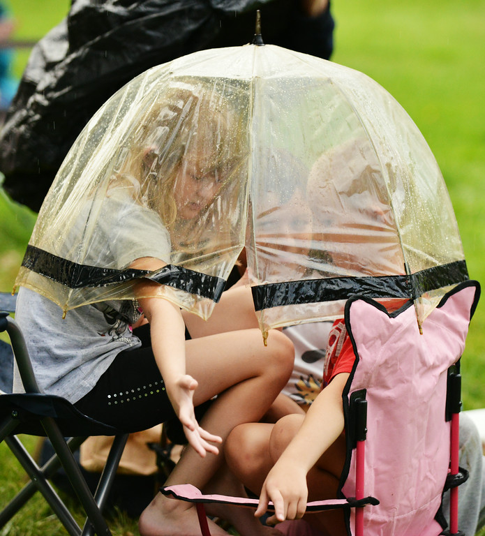Nine-year-old Rosi Anderson, left, Brandon Hernandez, 9, and Tyler Anderson, 7, sit under an umbrella together as rain pours down during Concert in the Park Tuesday evening at Kendrick Park. The Sheridan Press|Justin Sheely.