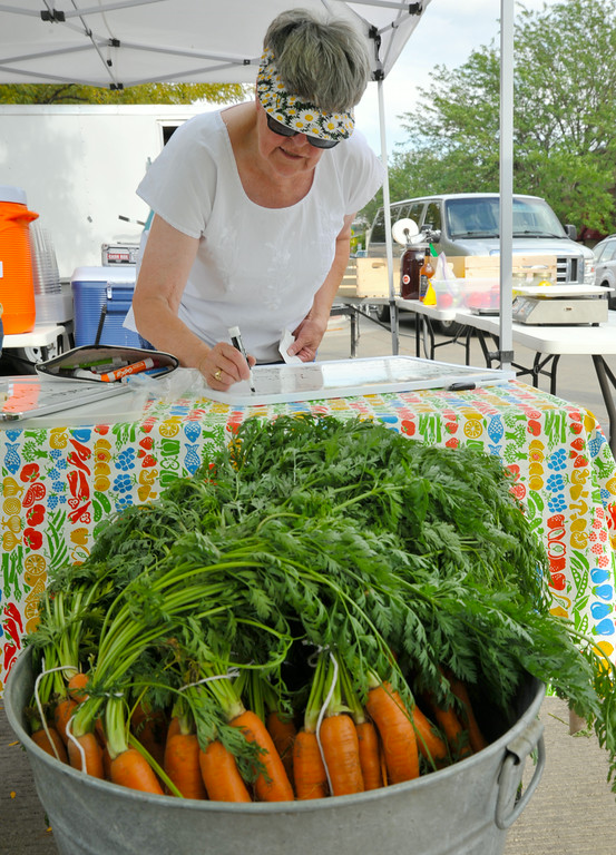 Peg Cullin writes down the products and prices on a white board for the Box Cross Road Farms vendor during setup for the Farmer's Market Thursday on Grinnell Street. The Sheridan Press|Justin Sheely.
