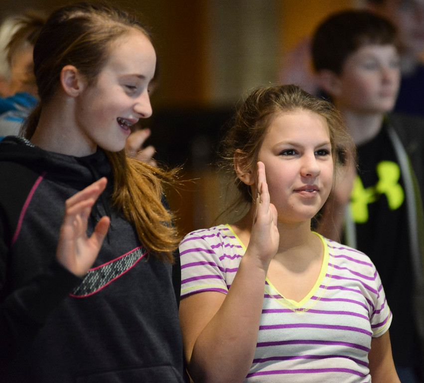 Sheridan seventh-graders Zoe Robison, left, and Nora Craft take the pledge during the Hands Off Drugs Program commitment ceremony Thursday afternoon at Sheridan Junior High School. The school had 226 students pledge to remain free of all harmful and illegal chemical substances. Students who made the pledge had done so after careful consideration and and interview by their school counselor. Family and friends of the students came to witness and support their students as they pledged to be drug-free and made handprints on the walls in hallway to show their commitment. The walls in the hallway near the school library are marked with hundreds of hand prints and signatures from students of years past who committed to remain drug-free.  Justin Sheely|The Sheridan Press.