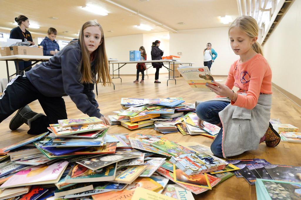 Seventh-grader Courtney Wallach, left, and Peyton McLaughlin, fourth grade, organize books for appropriate age groups for the Season's Readings program Friday at St Peter's Episcopal Church. The books will be distributed by the Food Group to children in schools across the county. The books were sorted into age groups and gift-wrapped by Big Horn Elementary's Adventure Club and Helping Hands as part of their service with the Food Group. The Season's Readings program is intended to provide children with gently used books to read and enjoy. Justin Sheely|The Sheridan Press.