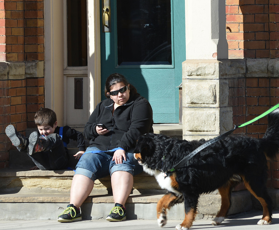 A walking dog greets Frany Lopez and her 3-year-old son as they wait for a friend to finish shopping Saturday morning on Main Street.