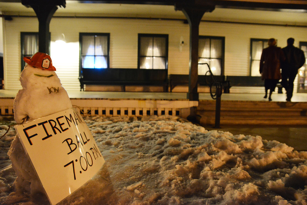 A snow-fireman holds a sign for the annual Fireman's Ball outside of the Sheridan Inn Saturday night.