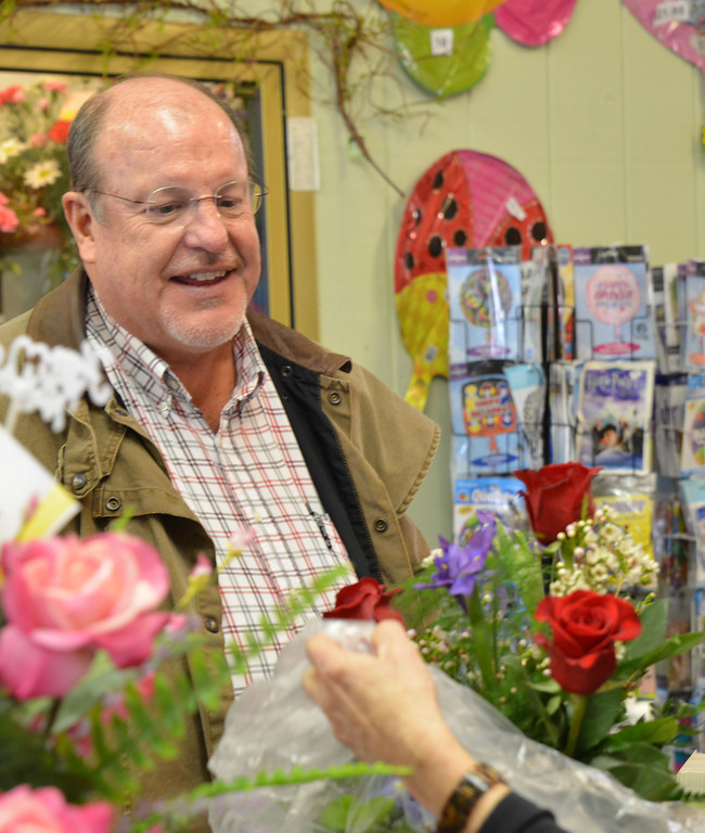 Terral Bearden watches as the clerk wraps his flower bouquet Wednesday at Annie Greenthumbs. Bearden bought the gift for his wife this Valentines day.