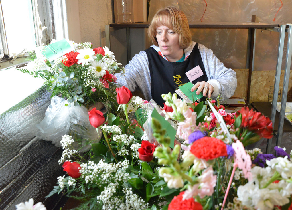 Jennifer Flannery rearranges vases of flowers for delivery Wednesday at Annie Greenthumbs. Valentines day is one of the busiest times in the year for the floral shop, which hires part-time help to keep up with the demand.