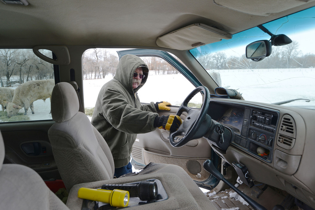 Toby Johnson enters his ranch truck to feed the livestock in the next field Tuesday at his ranch in Big Horn.