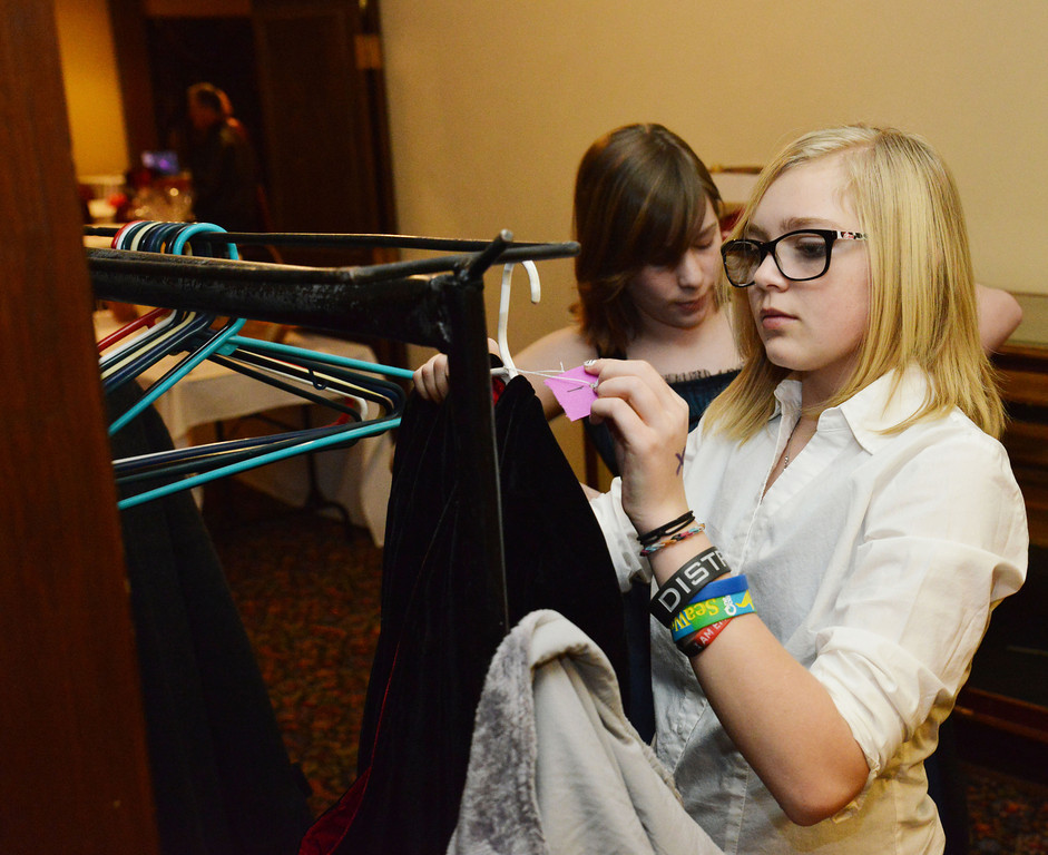 Seventh grader Nicole Mack checks in a guest's coat with the Girl Scouts Troop N0.1333 during the annual Fireman's Ball at the Sheridan Inn Saturday night. The fundraising event was to benefit the Sheridan Fire-Rescue firehouse.