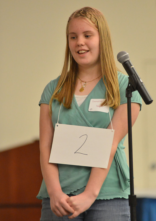 Emmalee Hoopes stands at the microphone as she correctly spells the word given by the Pronouncer and earning first place during the Sheridan County Spelling Bee Thursday at the Sheridan College Presentation Hall.