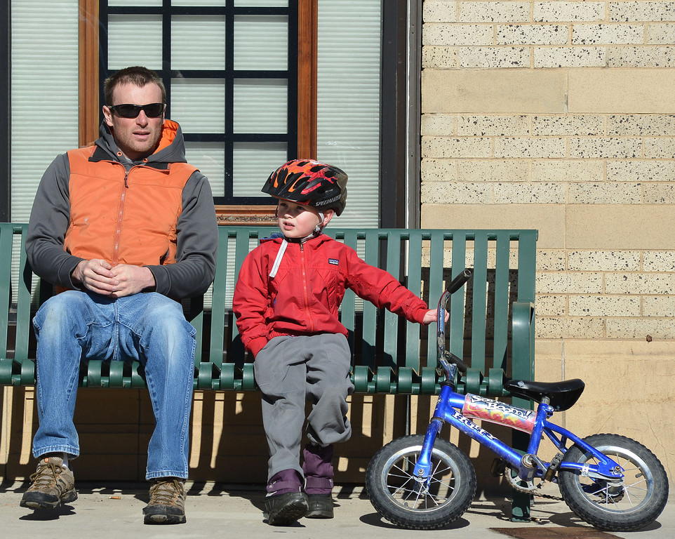 Hermes Lynn takes a break from bike riding with his 4-year-old son Sully Lynn during a warm Saturday morning on Main Street.