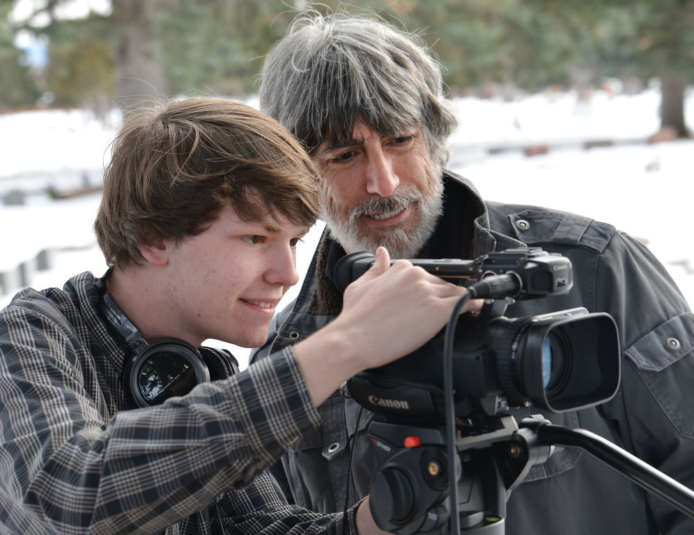 """Sheridan High School Broadcast Journalism student Jace Dahlin, left, and teacher Michael Clift check the camera before shooting a scene last week at the Sheridan Municipal Cemetery. The video short will be used as a visual element in the upcoming theater performance """"Grease,"""" which shows at the Sheridan High School auditorium Wednesday, March 5th through Saturday, March 8th at 7:30p.m. and on Sunday, March 9th at 2:00p.m."""